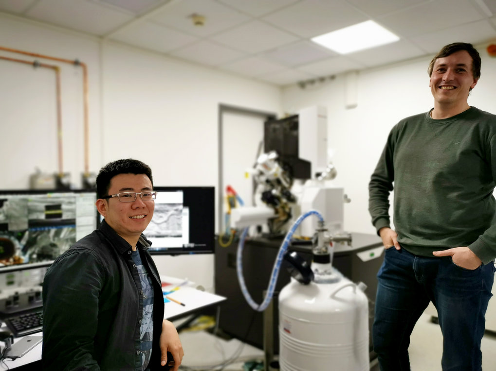 """This is us with our 'machine', the Aquilos cryo-FIB/SEM. It helps us to make the hidden biology visible. The Aquilos is used to thin down thick samples with a focused ion beam. These thin regions are then imaged with a cryo-TEM."" Sebastian Tacke and Zhexin Wang, scientists  Structural Biochemistry"